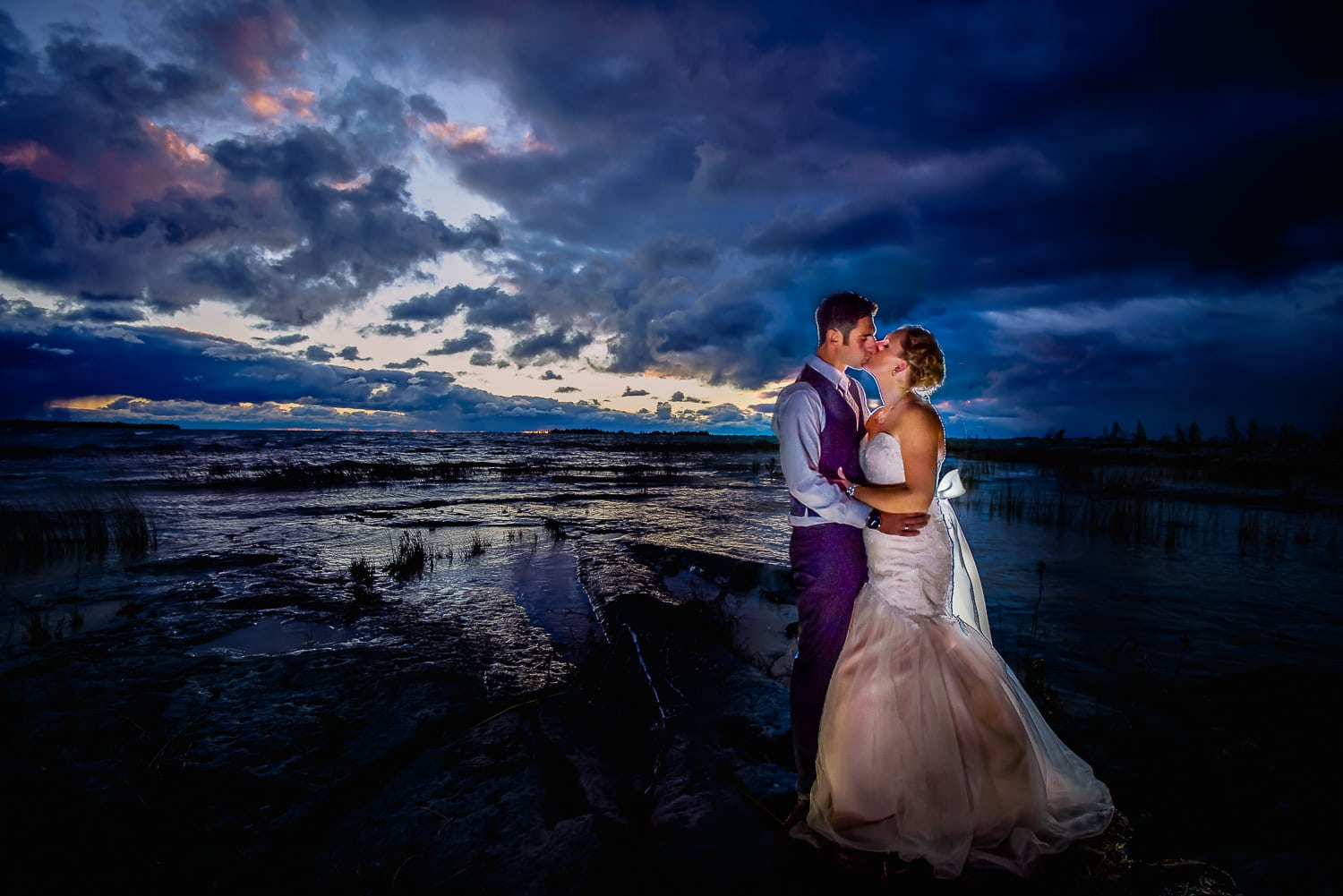 Bride and groom on beach after dusk
