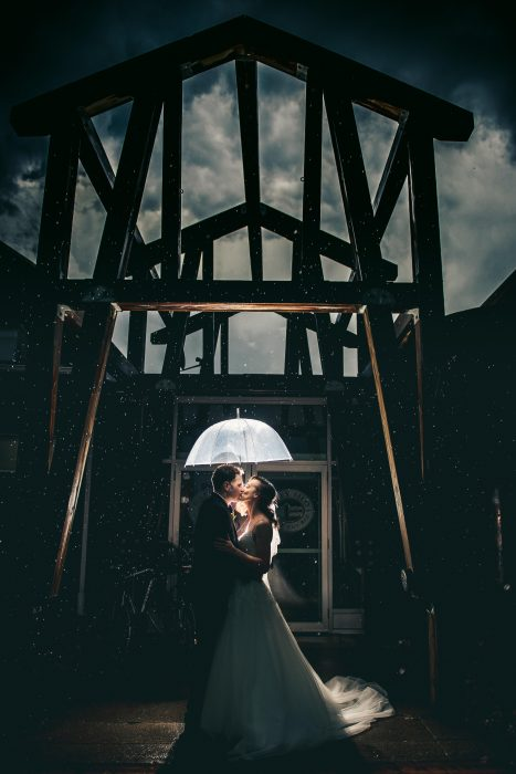 Night shot with rain and dramatic clouds bride and groom holding umbrella