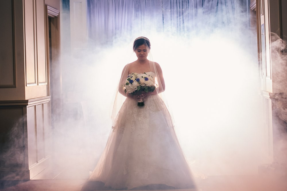 Bride coming down aisle at her wedding at brookside banquet centre with fog machine