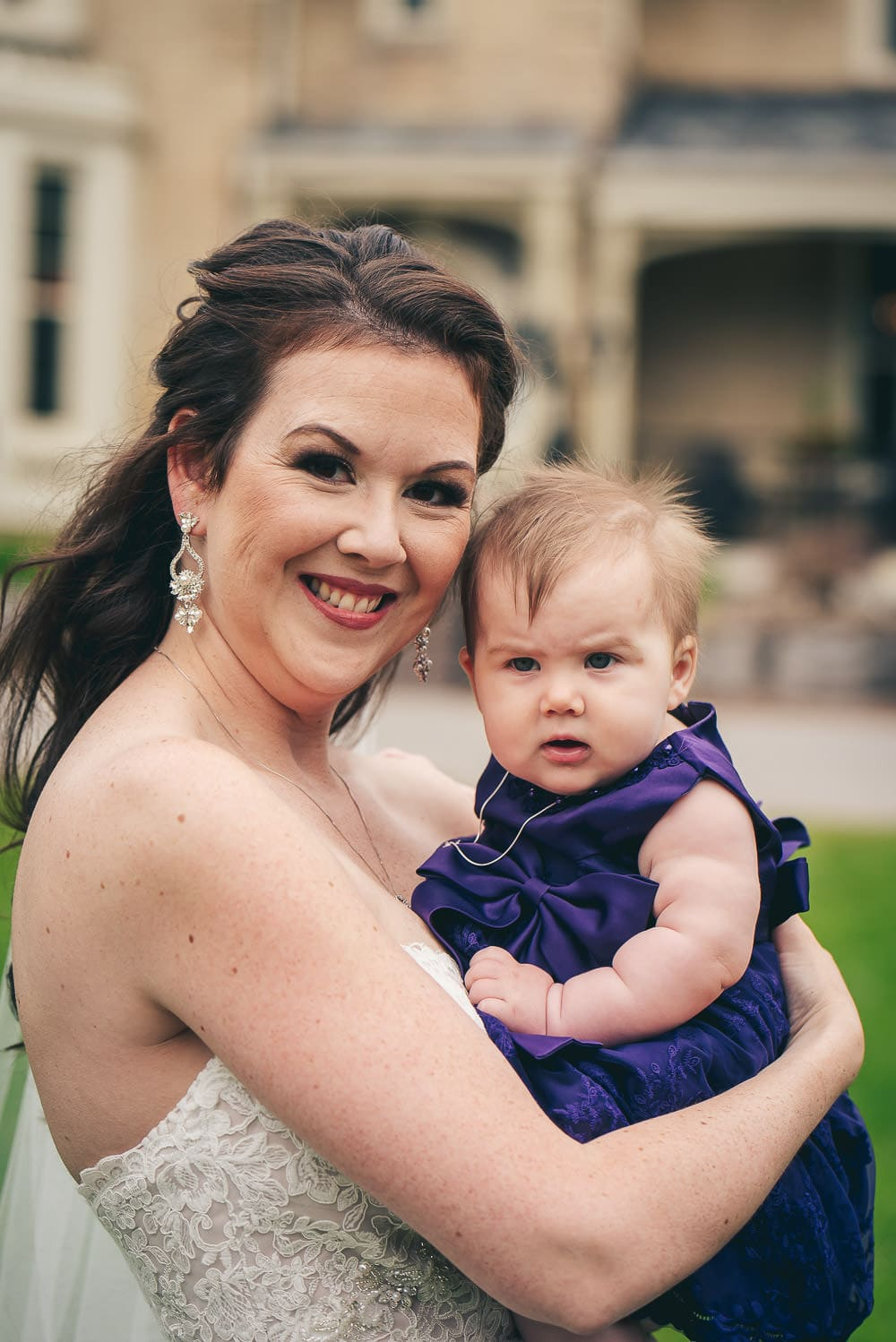 bride posing for picture with her daughter before wedding in front of the Elmhurst Inn