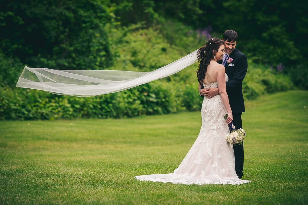 bride and groom posing for wedding photo in the valley at the Elmhurst Inn  with veil blowing in the wind