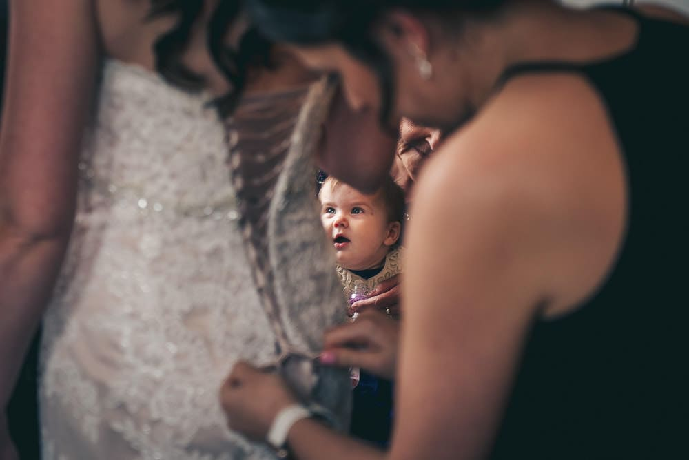 baby looking at mom getting ready for wedding at Elmhurst Inn