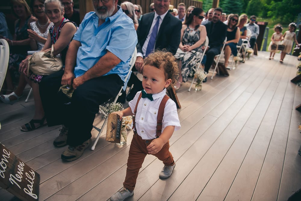 ring bearer marching down the aisle at pine Vally chalet