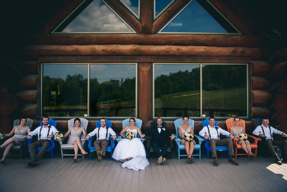 wedding party sitting on muskoka chairs on deck at pine valley chalet