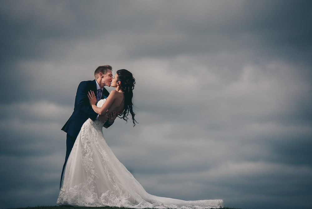 bride and groom kissing in the sky