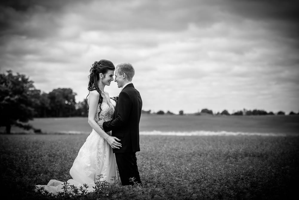 bride and groom in field in black and white at Mitchel golf club
