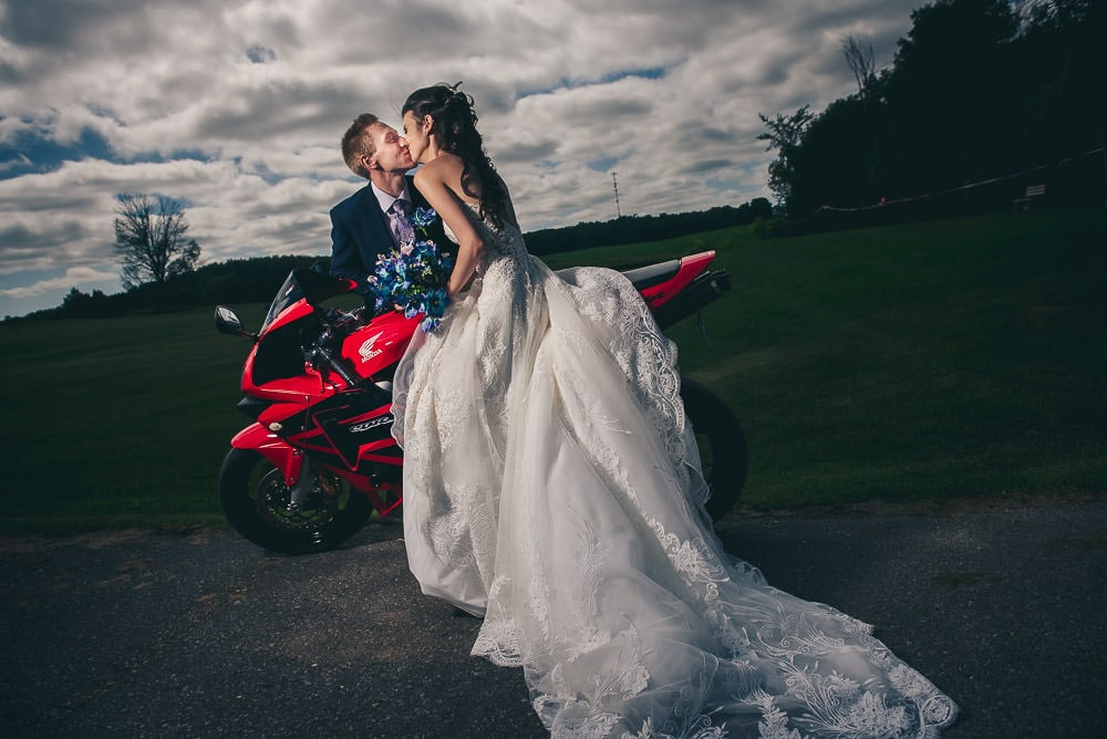 bride and groom kissing on motorbike at their wedding at Mitchel Golf club