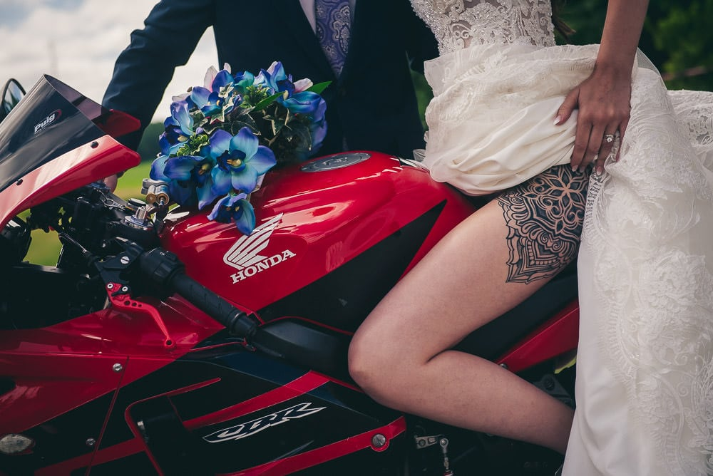 wedding photo showing off brides tattoo on motorcycle at Mitchell golf course
