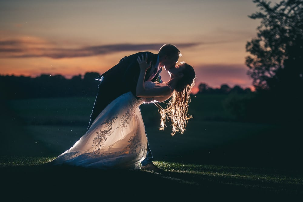 sunset wedding photo bride and groom doing dip kiss at Mitchel golf course