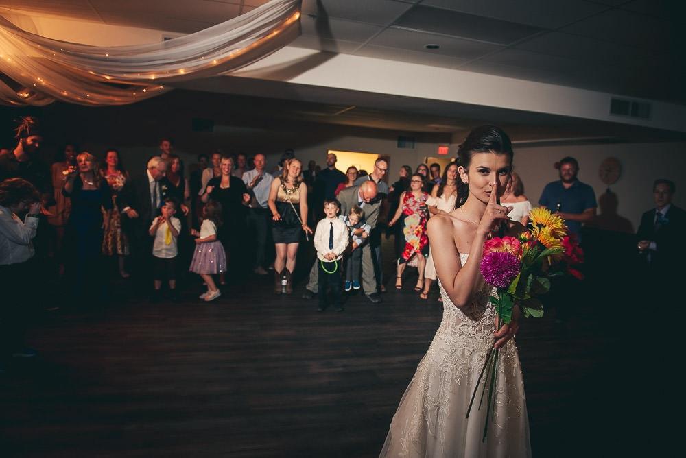 bride throwing the bouquet at her wedding at Mitchell Golf Course