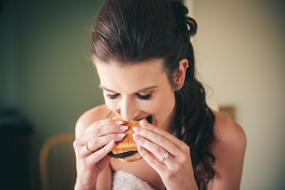 bride enjoying a burger before her wedding