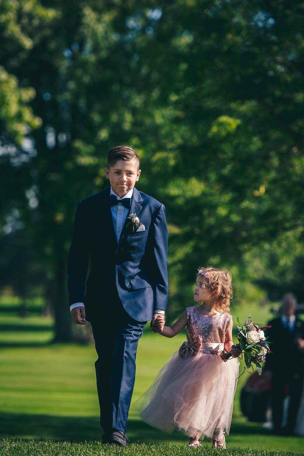 nick and Courtneys kids walking down the aisle during wedding at craigowan golf club