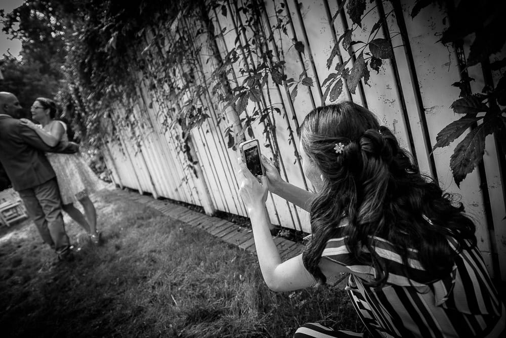 daughter taking photo of mom at backyard wedding in toronto