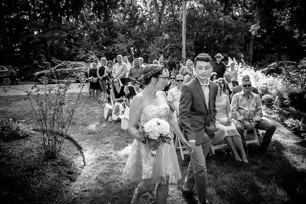son walking mom down the aisle at backyard wedding in Toronto